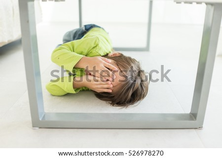 Kid covering his face under the table at home