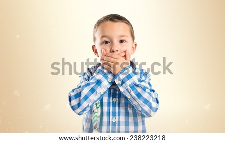 Kid covering his mouth over ocher background  - stock photo