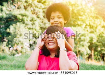 Kid covering mother's eyes in the green park with copy space - Daughter and mother relationship