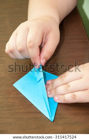 Kid creating origami airplane on the table. - stock photo