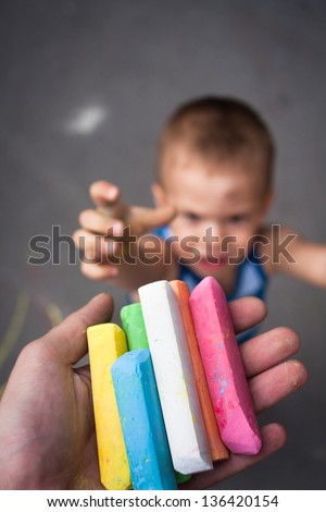 Kid crying for chalk on a street playground - stock photo