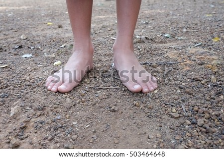 Kid dirty feet on barren dry arid ground.  Bare feet on ground