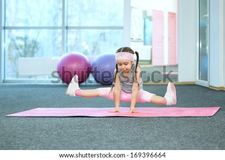 Kid doing fitness exercises on the mat - stock photo