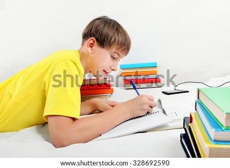 Kid doing Homework on the Bed in the Room - stock photo
