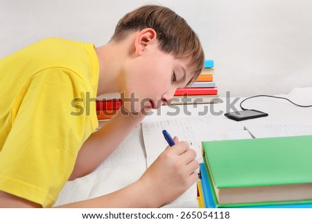 Kid doing Homework on the Sofa at the Home - stock photo