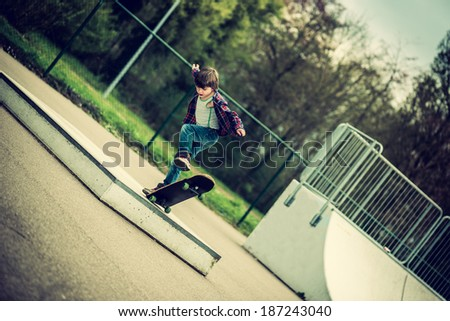 kid doing tricks on his skateboard, vintage effect added - stock photo