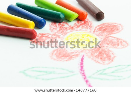 Kid drawing flower picture using crayons on white background - stock photo