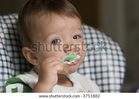 Kid eating by himself - stock photo