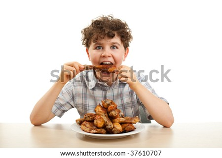 Kid eating chicken drumsticks isolated on white