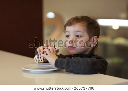 Kid eating eclair at table in the cafe - stock photo