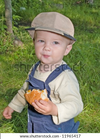 kid eating the roll in the park outdoor