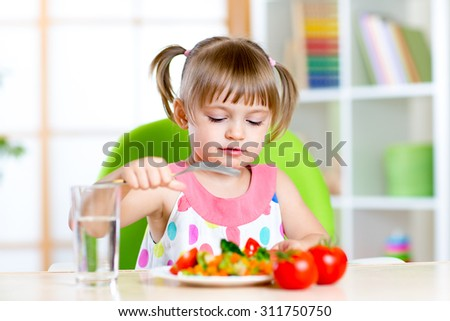 Kid eats fresh vegetables. Healthy eating for child.