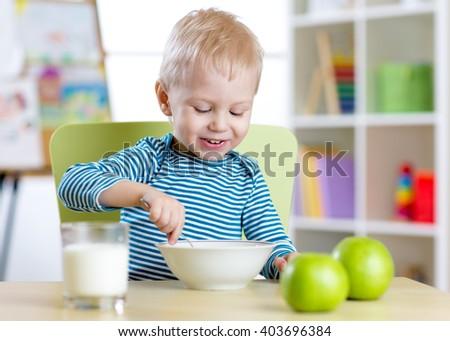 kid eats healthy food at home or kindergarten - stock photo