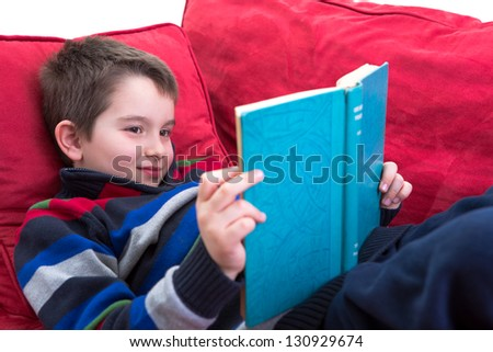 Kid enjoy reading the novel on the comfortable red couch. - stock photo