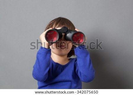 kid exploration concept - focused 4-year old child with bob cut in watching through binoculars for discovery and imagination,studio shot - stock photo