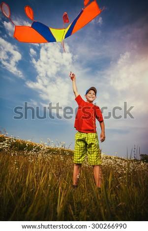 Kid flies a kite into the blue sky - stock photo