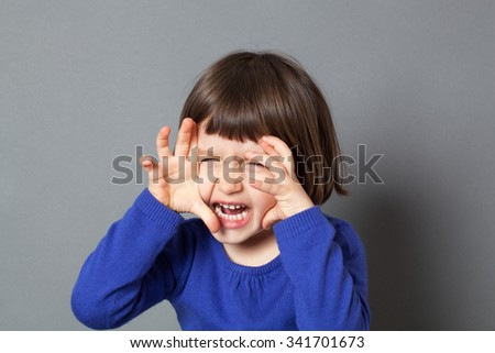 kid fun concept - energetic preschool child playing like a monster or tiger roaring with hands like claws for scary game,studio shot