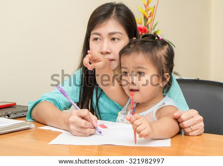 kid girl and her mom reading and writing a book together