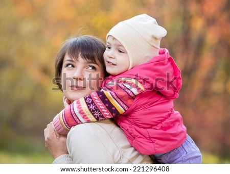 Kid girl and her mother in the autumn park - stock photo