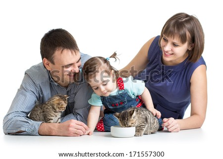 kid girl and her parents feeding small kittens - stock photo