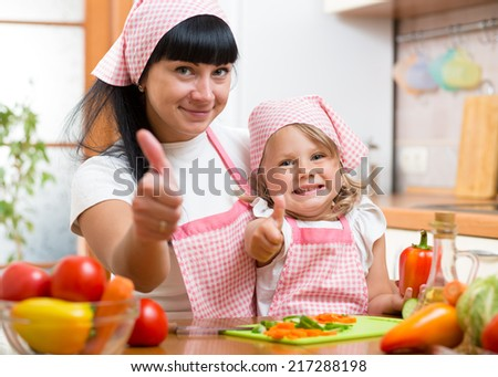 Kid girl and mother cooking and showing thumb up - stock photo