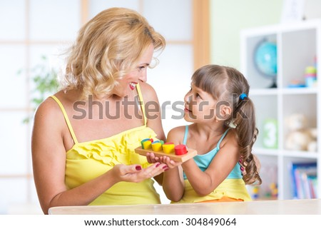 kid girl and mother playing at table at home