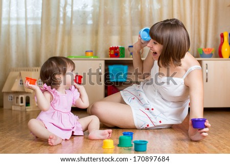 kid girl and mother playing together with cup toys - stock photo