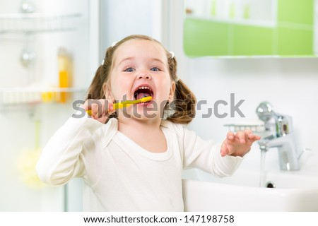kid girl brushing teeth in bathroom - stock photo