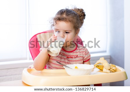 kid girl eating corn flakes with milk - stock photo