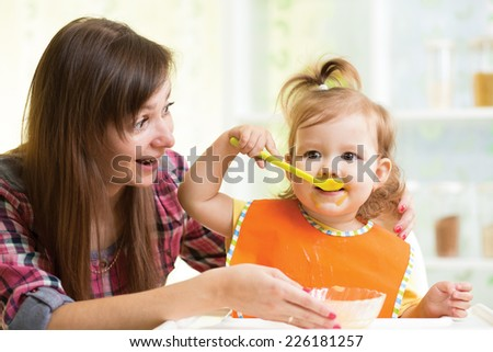 kid girl eating with spoon indoors at kitchen