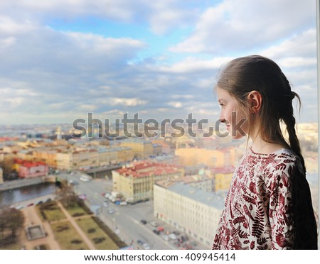Kid girl enjoying scenic View of St. Petersburg from the roof with dramatic sky - stock photo