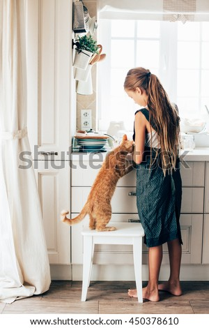 Kid girl feeding ginger cat at the kitchen
