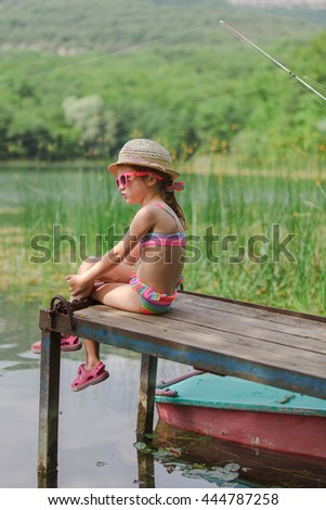 kid girl in sunglasses sitting on the wood bridge near boat and  - stock photo