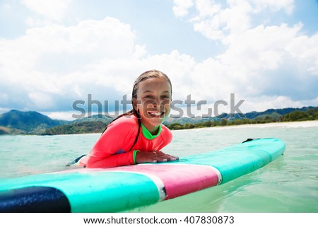 Kid girl is learning surfing