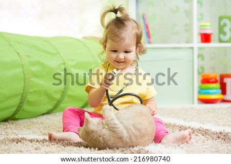 Kid girl playing doctor with kitten - stock photo