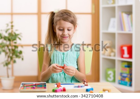 Kid girl playing modeling plasticine or molding clay in nursery - stock photo