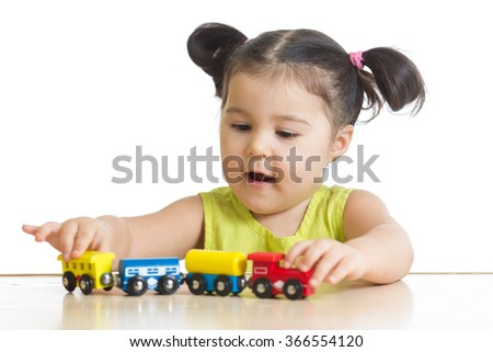 Kid girl playing with train toy isolated on white - stock photo