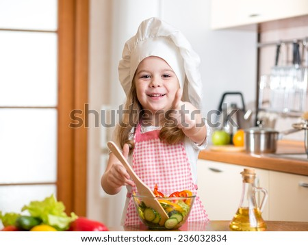 kid girl preparing healthy food and showing thumb up - stock photo