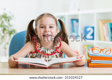 kid girl reading a book at nursery