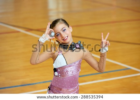 kid girl rhythmic gymnastics on wooden deck medal winner gesture - stock photo