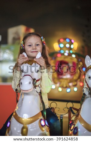 Kid girl riding on a carousel horse - stock photo