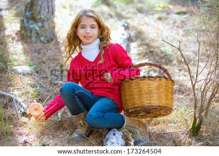 kid girl searching chanterelles mushrooms with basket in autumn forest