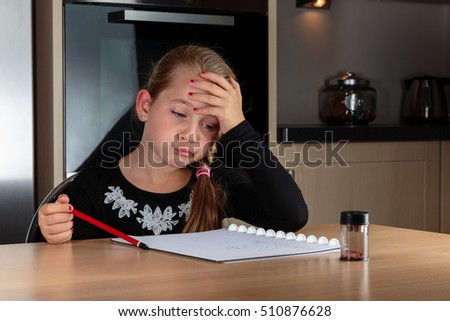 Kid (Girl) thinking while doing her homework and holding a pencil