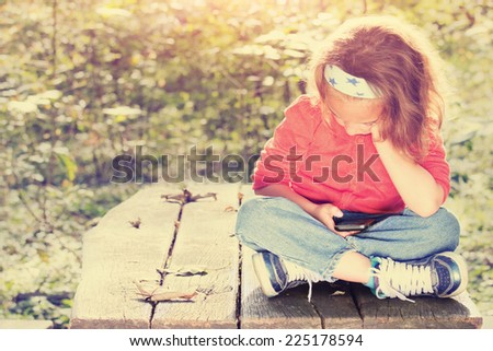 Kid girl using smart phone on a park bench. - stock photo