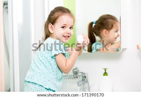 kid girl washing hands in bathroom - stock photo