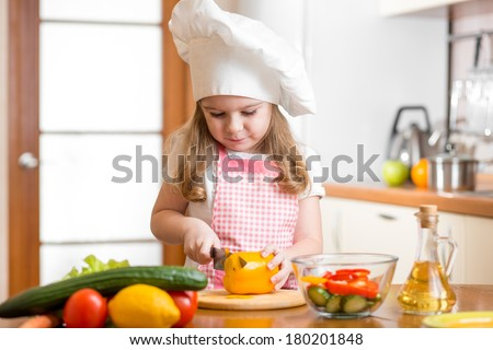 Kid girl weared as cook cutting vegetables - stock photo