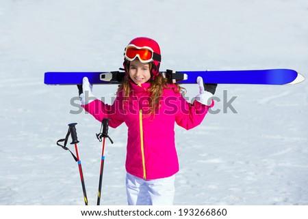 Kid girl winter snow holding ski equipment helmet goggles poles - stock photo