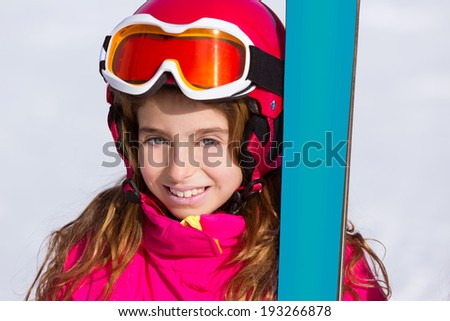 Kid girl winter snow portrait with ski equipment helmet and goggles - stock photo