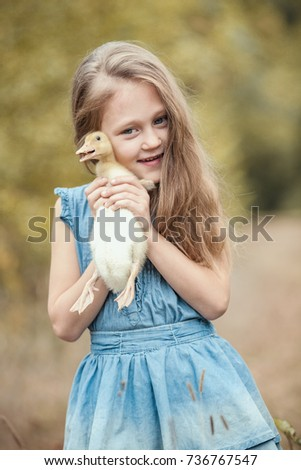 Kid girl with duckling in hands