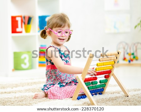 kid girl with eyeglasses playing abacus toy - stock photo
